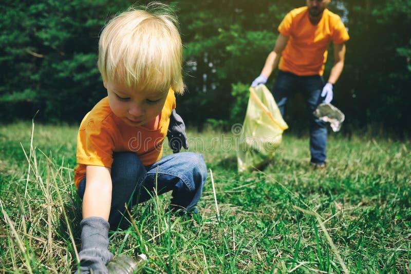 Volunt?rios que pegaram a maca no parque O pai e seu filho da criança que limpam o rapaz pequeno da floresta recolhem o lixo plás foto de stock
