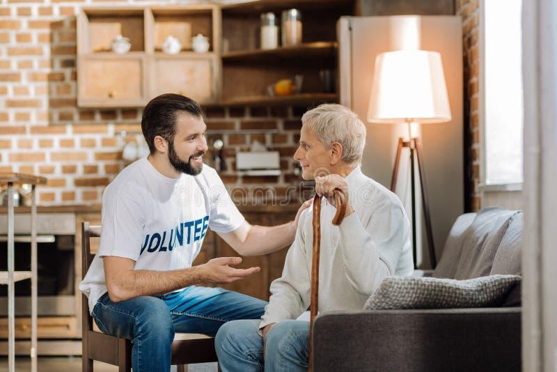 Voluntario atento joven que dice el último nuevo a un hombre mayor fotos de archivo libres de regalías