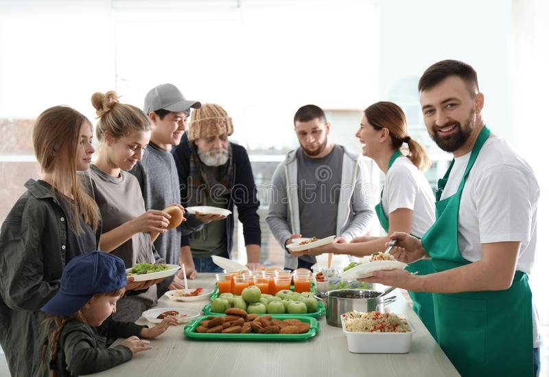 Voluntario con el colega que da la comida a la gente pobre imagenes de archivo