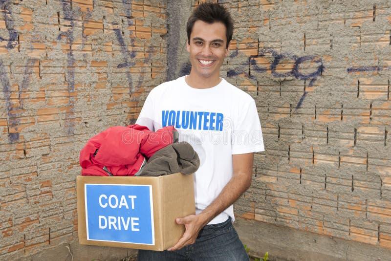 Voluntario con el rectángulo de la donación del mecanismo impulsor de la capa foto de archivo libre de regalías