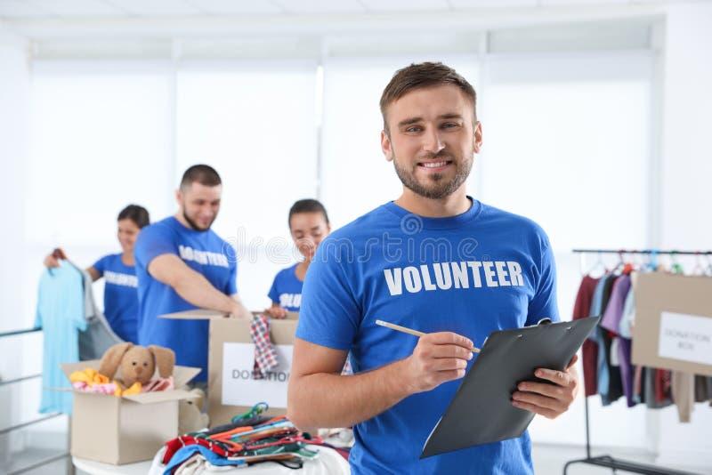 Voluntario del varón con donaciones del anuncio del tablero imágenes de archivo libres de regalías