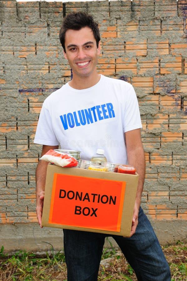 Voluntario feliz con el rectángulo de la donación del alimento fotografía de archivo libre de regalías