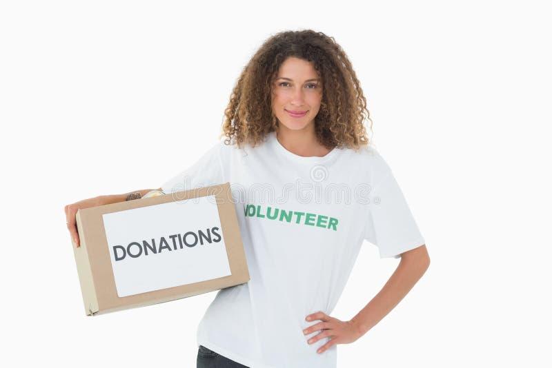 Voluntario feliz que lleva a cabo una caja de donaciones con la mano en cadera imágenes de archivo libres de regalías