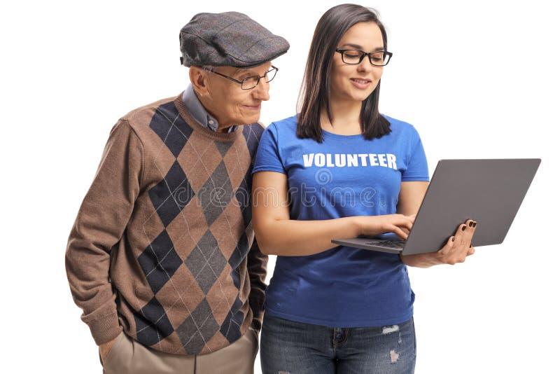 Voluntario femenino joven con un ordenador portátil que ayuda a un hombre mayor con tecnología foto de archivo libre de regalías