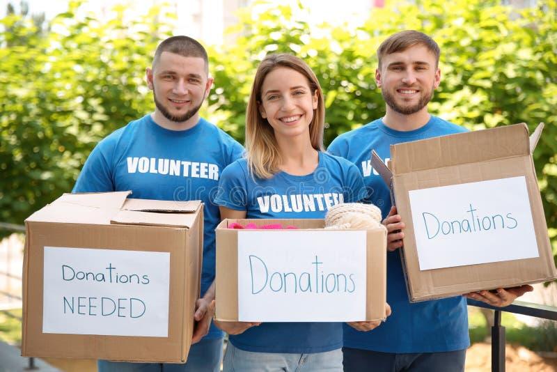 Voluntarios de los jóvenes que sostienen las cajas con donaciones foto de archivo