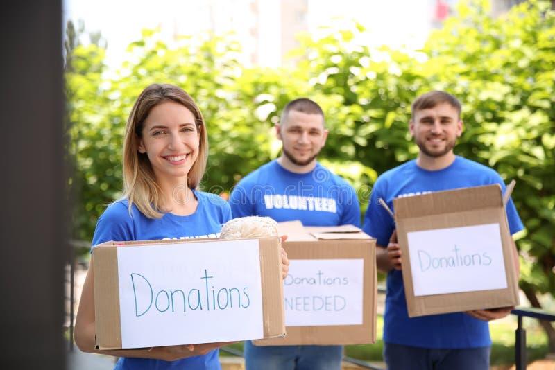 Voluntarios de los jóvenes que sostienen las cajas con donaciones imagenes de archivo