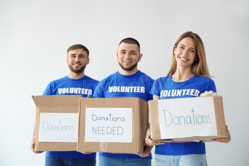 Voluntarios de los jóvenes que sostienen las cajas con donaciones fotografía de archivo