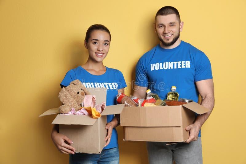 Voluntarios de los jóvenes que sostienen las cajas con donaciones imagen de archivo libre de regalías