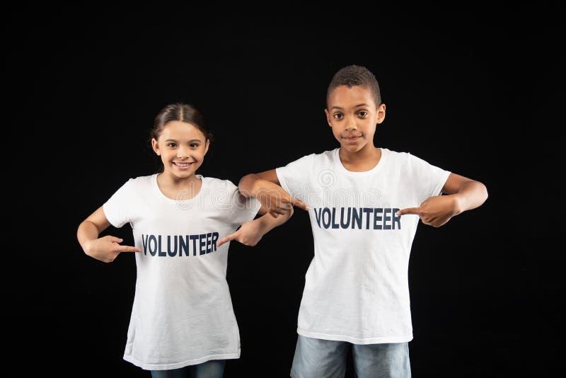 Voluntarios inspirados de los jóvenes que llevan las camisas blancas foto de archivo