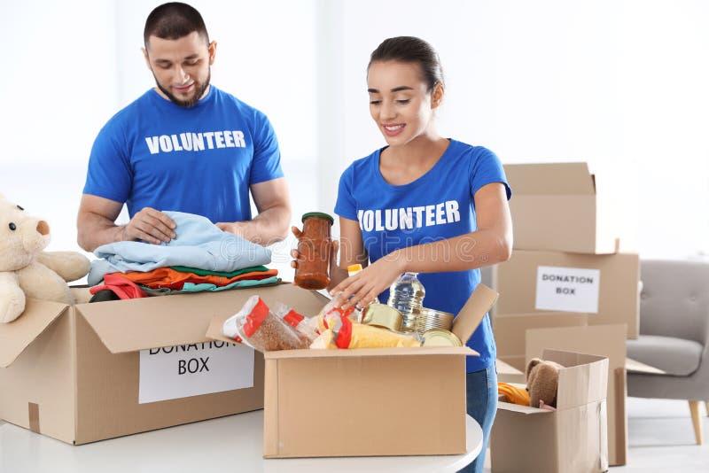 Voluntarios jovenes que recogen donaciones fotos de archivo libres de regalías