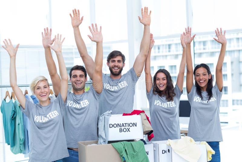 Voluntarios que aumentan sus manos foto de archivo