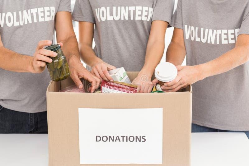 Voluntarios que clasifican donaciones foto de archivo