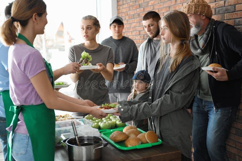 Voluntarios que dan la comida a la gente pobre imagen de archivo libre de regalías