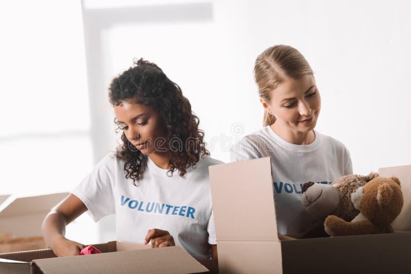 Voluntarios que embalan los juguetes para la caridad fotos de archivo