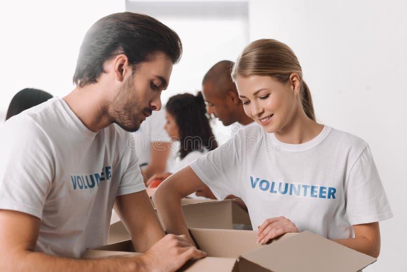 Voluntarios que embalan mercancías en caja fotografía de archivo