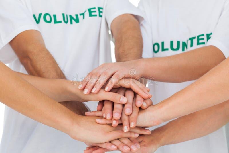 Voluntarios que llenan para arriba sus manos juntas imagen de archivo libre de regalías