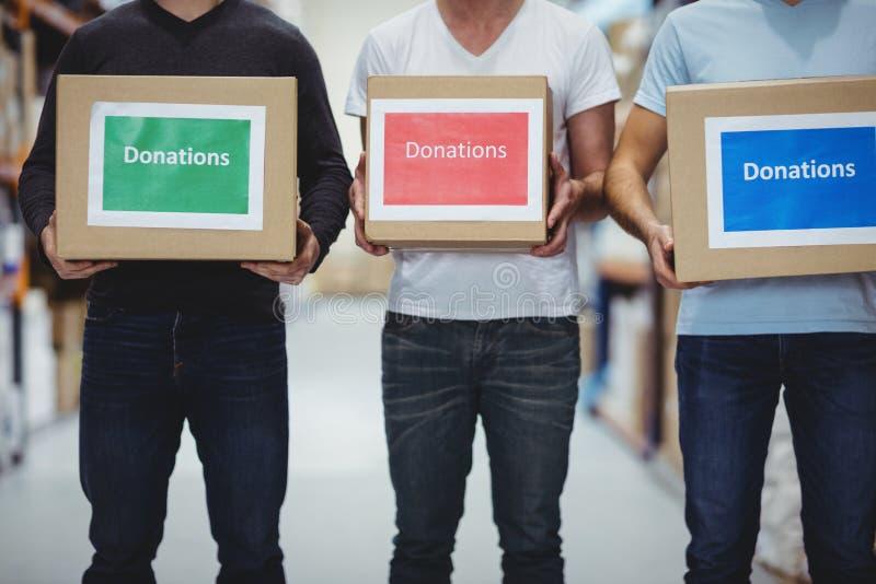 Voluntarios que sonríen en la cámara que sostiene las cajas de las donaciones foto de archivo libre de regalías