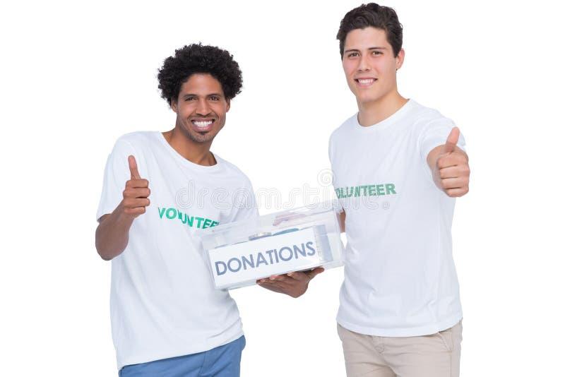 Voluntarios sonrientes jovenes que recogen donaciones foto de archivo libre de regalías