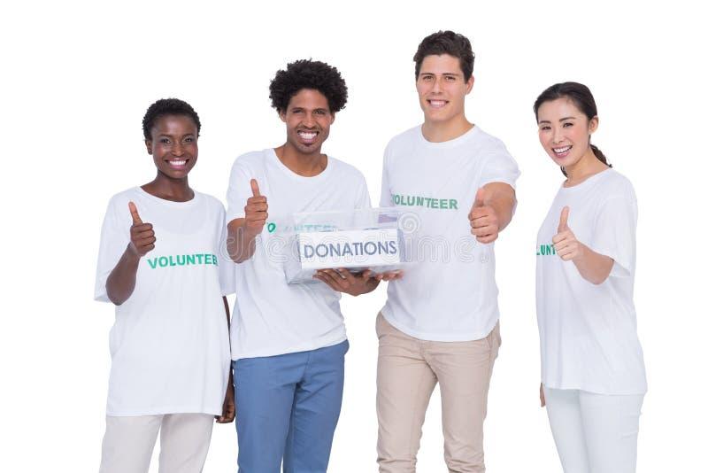 Voluntarios sonrientes jovenes que recogen donaciones imagenes de archivo