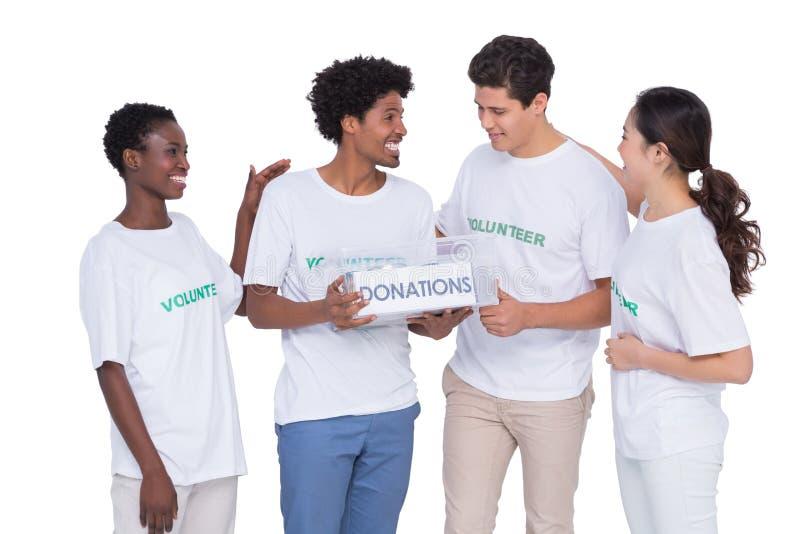 Voluntarios sonrientes jovenes que recogen donaciones fotografía de archivo