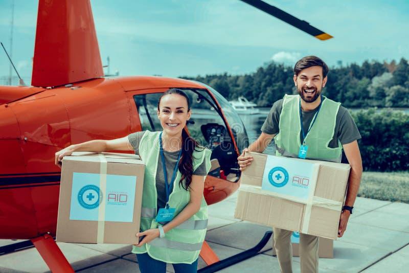 Voluntarios trabajadores apuestos felices que llevan las cajas pesadas con la ayuda imagen de archivo