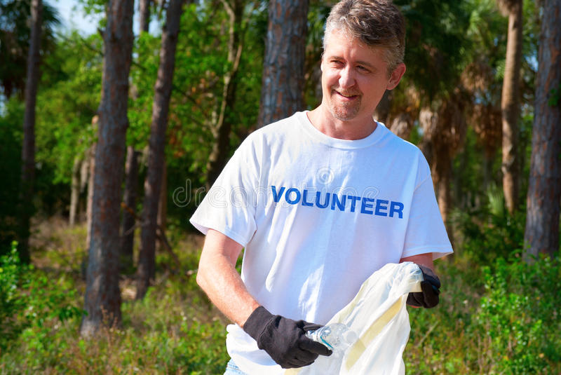 Volunteer beach park environmental cleanup. Man picking up litter during a volunteer environmental cleanup event stock images