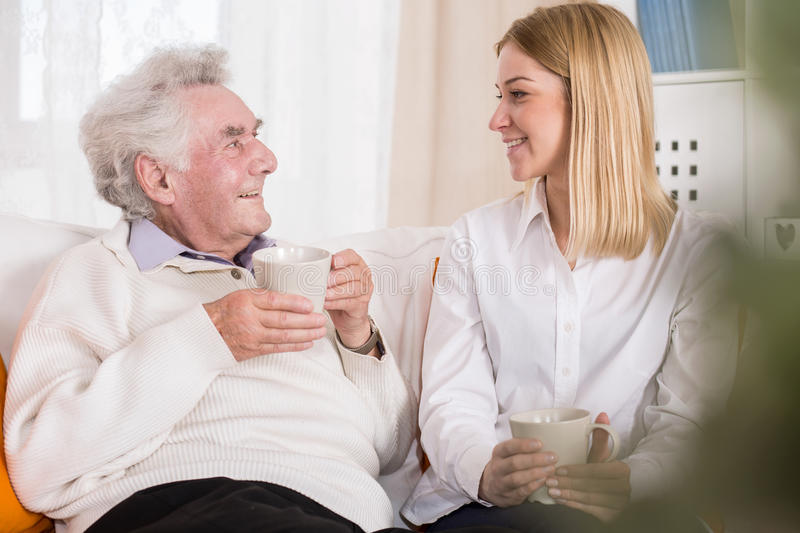 Volunteer in care home. Photo of volunteer in care home talking with old man stock photo