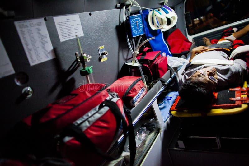 Volunteer EMTs. An injured motorcycle driver lies on a stretcher inside a Sawang Prateep`s ambulance stock photos