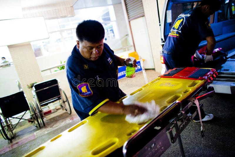 Volunteer EMTs. A member of Sawang Prateep Emergency Medical Service cleans a stretcher with alcohol after it was used to transport an injured motorcycle driver stock photography