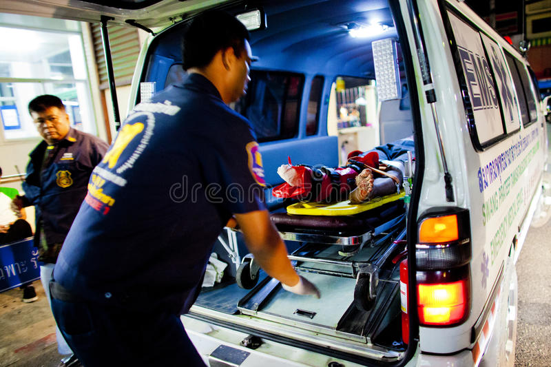 Volunteer EMTs. A member of Sawang Prateep Emergency Medical Service removes an injured motorcycle driver from an ambulance stock image