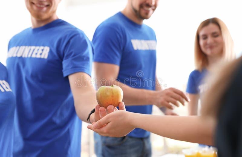 Volunteer giving apple to poor person. Closeup stock photo