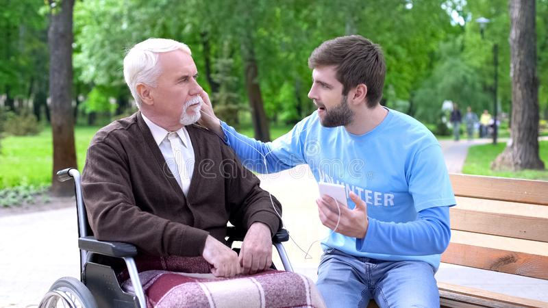 Volunteer and handicapped elderly man listening motivate podcast together. Volunteer and handicapped elderly men listening motivate podcast together, stock photo stock images