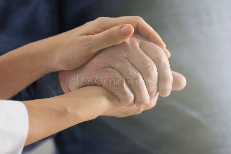 Volunteer holding hand of senior man. Closeup stock photos