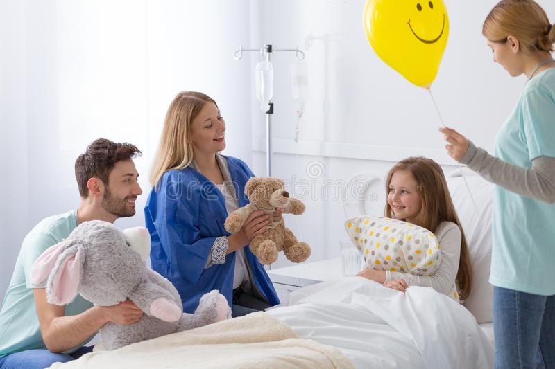 Volunteer in the hospital making sick girl happy stock image