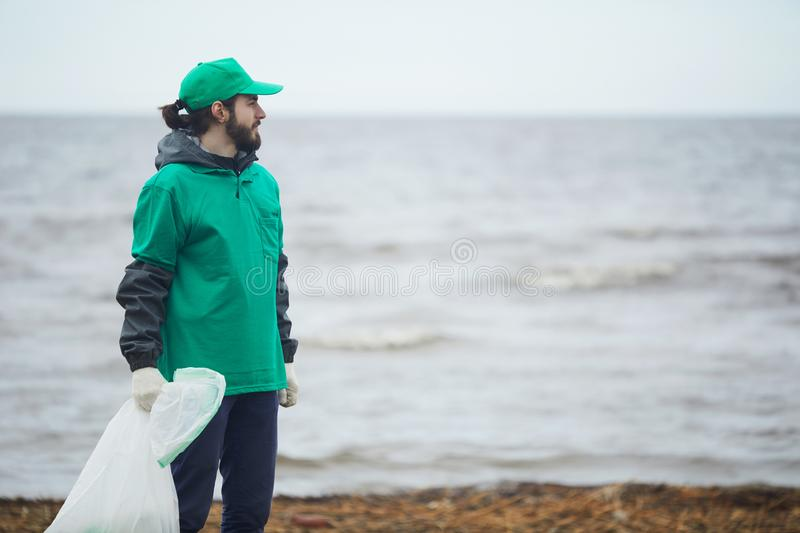 Volunteer looking away on coast. Young volunteer man in green uniform with bag standing on coast and looking away royalty free stock photo