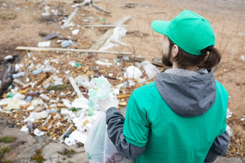 Volunteer man at garbage pile. Back view of volunteer man in green uniform standing with bag at pile with trubbish stock photos