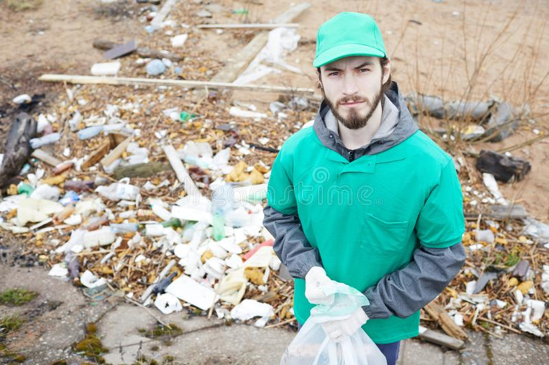 Volunteer man at pile of litter. Young volunteer in green uniform standing at pile of litter and looking at camera with confidence stock photography