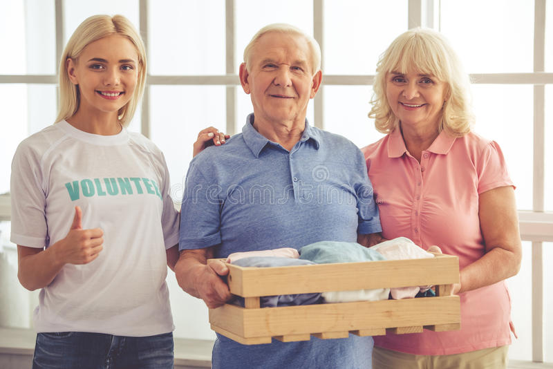 Volunteer and old people. Beautiful young female volunteer and old couple are looking at camera and smiling. Couple is holding a box of new clothes stock photo