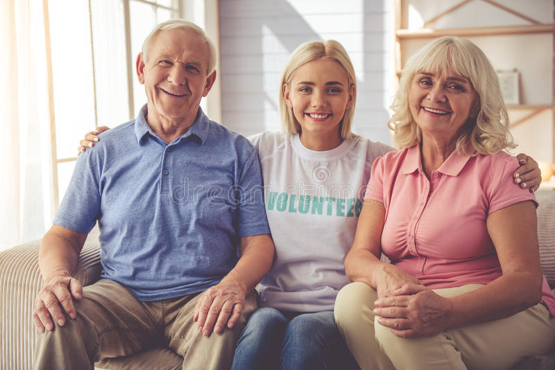 Volunteer and old people. Beautiful young female volunteer and old couple are looking at camera and smiling while sitting on couch royalty free stock photos