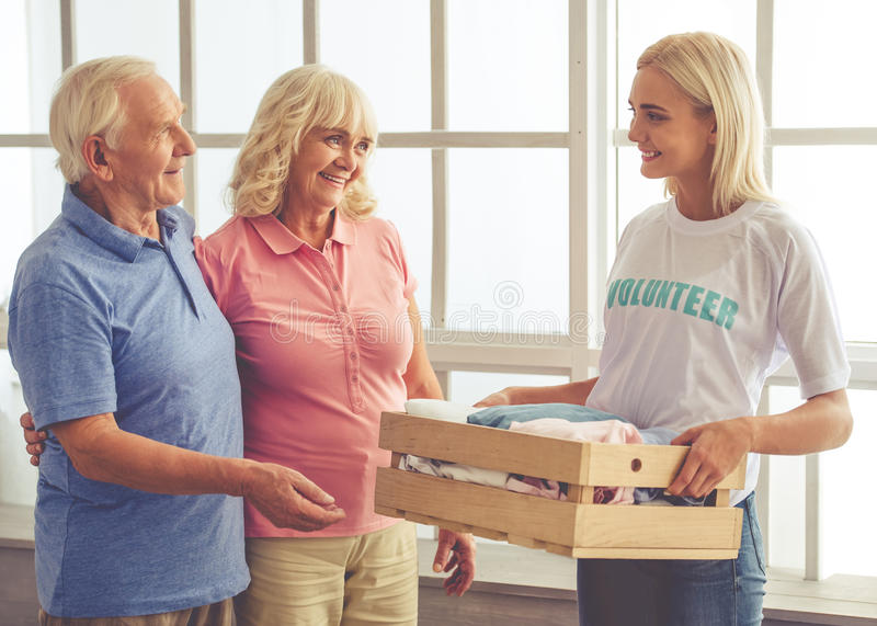 Volunteer and old people. Beautiful young female volunteer is giving a box of new clothes to the old couple and smiling stock image