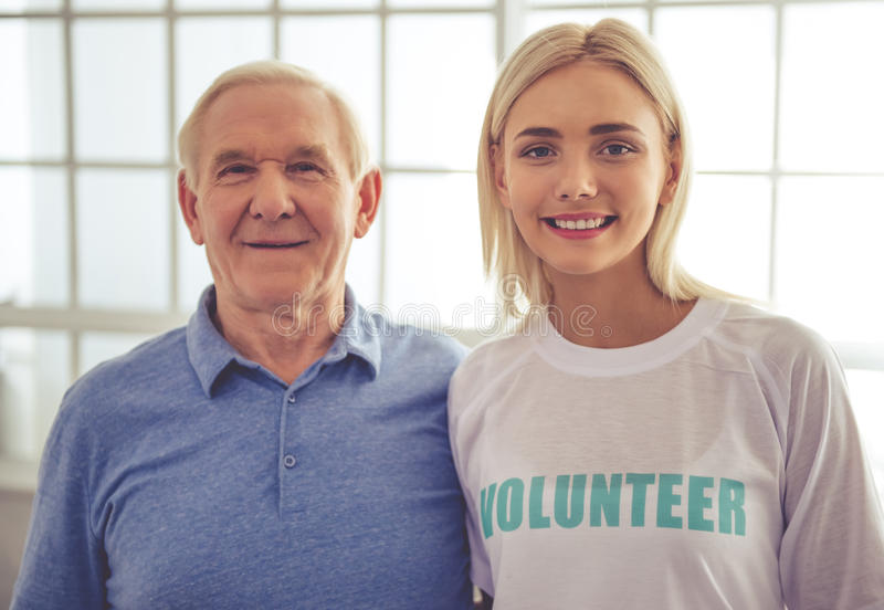 Volunteer and old people. Beautiful young female volunteer and handsome old men are looking at camera and smiling stock photo