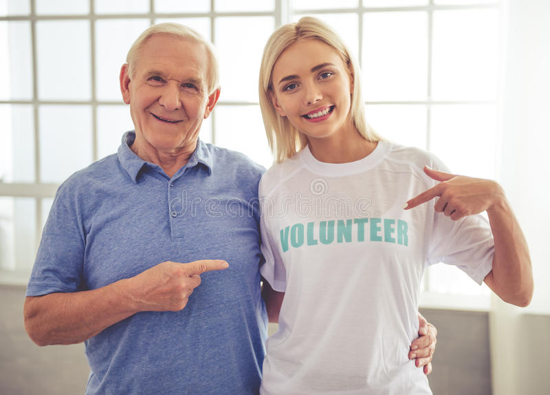 Volunteer and old people. Beautiful young female volunteer and handsome old men are pointing on the t-shirt, looking at camera and smiling royalty free stock photography