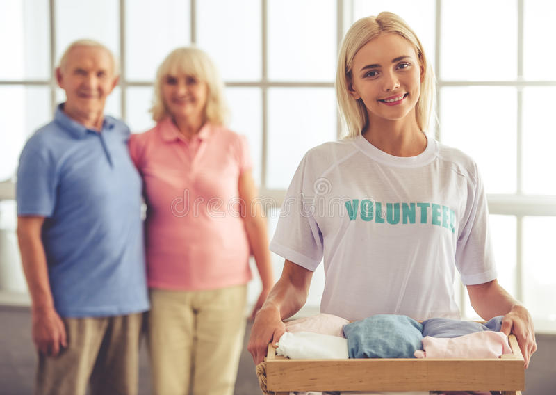 Volunteer and old people. Beautiful young female volunteer is holding a box of new clothes for the old couple and smiling. Couple in the background stock photo