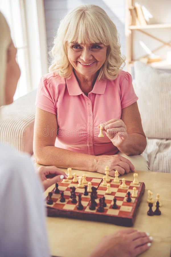 Volunteer and old people. Beautiful young girl-volunteer and beautiful old women are playing chess and smiling stock images