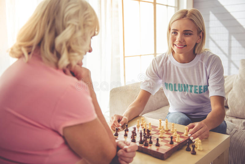Volunteer and old people. Beautiful young girl-volunteer and beautiful old women are playing chess and smiling stock image