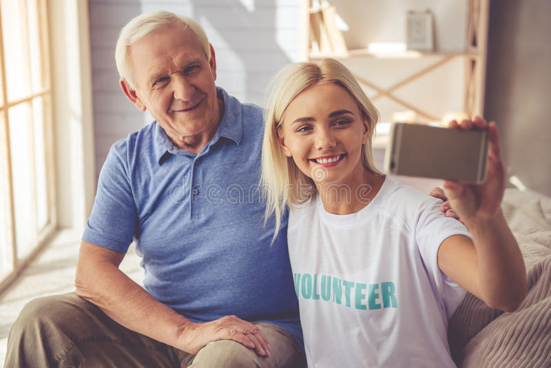 Volunteer and old people. Beautiful young girl volunteer and handsome old men are doing selfie using a smart phone and smiling while sitting on couch stock photography