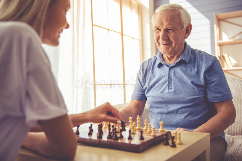 Volunteer and old people. Beautiful young girl-volunteer and handsome old men are playing chess and smiling stock image