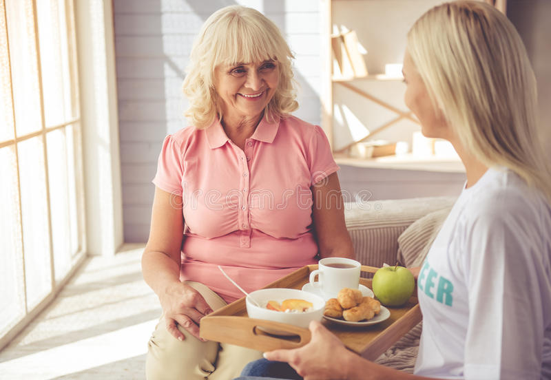 Volunteer and old people. Young girl volunteer is giving food to beautiful old women and smiling while sitting on couch stock photography