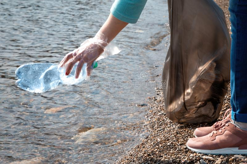 Volunteer pulls a plastic bottle from the sea. Concept of preservation of ecology and environmental cleanliness. Close up royalty free stock photos