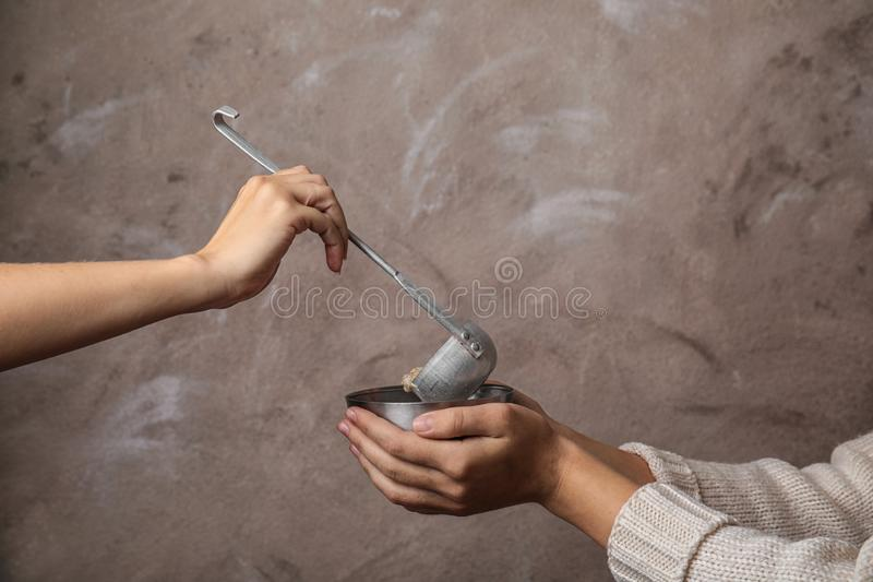 Volunteer putting food into bowl of poor woman stock image